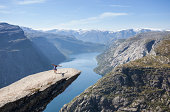 female gymnast doing a handstand on trolltunga rock above lake in norway
