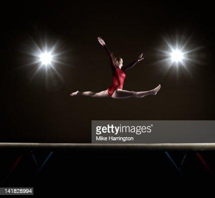 Female Gymnast Doing Mid Air Splits : Stock Photo