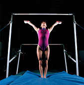 Female gymnast in front of asymmetric bars, arms raised
