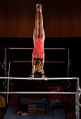 Female Gymnast Pauses In A Handstand At The Top Of Uneven Bars