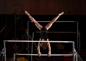 Female Gymnast Pauses In A Handstand On The Top Of Uneven Bars