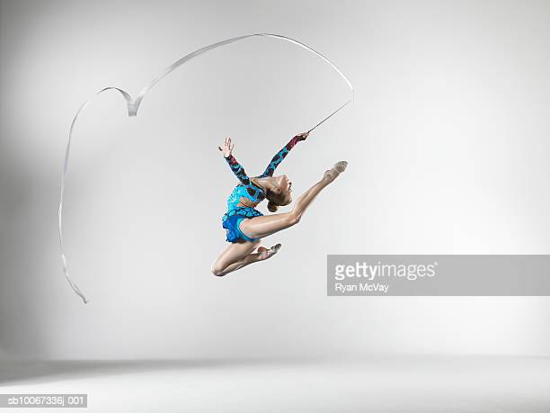 Female gymnast (14-15) leaping with dance ribbon, studio shot