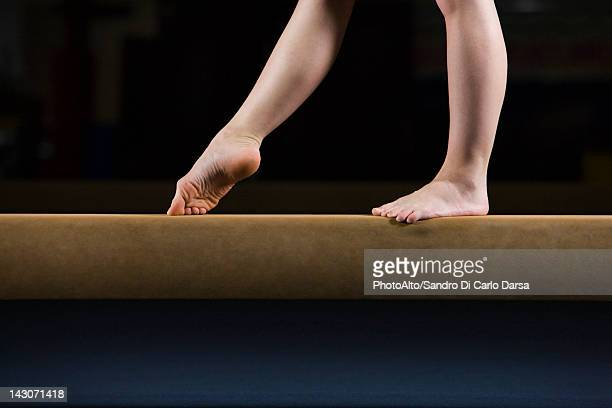 Female gymnast on balance beam, low section