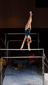 Female Gymnast On The Top Of Uneven Bars. She is gripping the bar one handed, twisting and switching her grip.