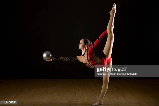 Female gymnast performing rhythmic floor routine with ball