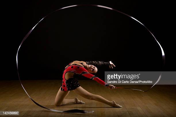 Female gymnast performing rhythmic floor routine with ribbon