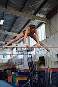 Female athlete training on bars at a local gymnastics club