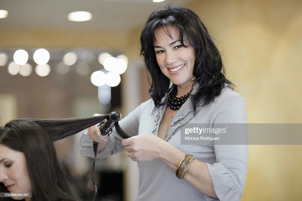 Female hair stylist drying female customer's hair in hair salon : Stock Photo