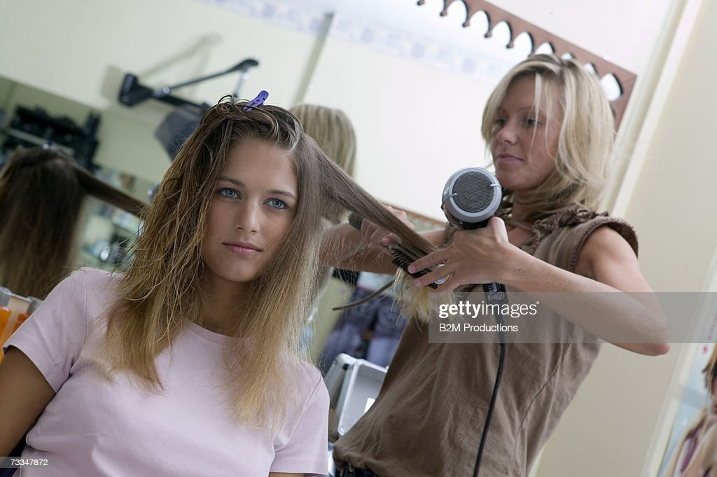 Female hair stylist drying young woman's hair : Stock Photo
