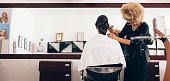 Hairdresser styling the hair of a customer at salon. Female hair stylist setting hair in fashionable design using a comb.