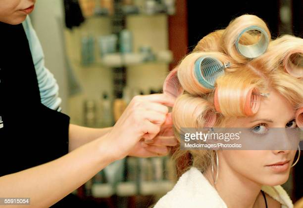 Female hairdresser adjusting curlers in a mid adult woman's hair