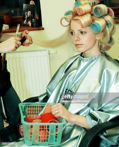 Female hairdresser cutting hair of a mid adult woman