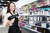Young female hairdresser in apron  holding blow dryer and hair cutters in shop