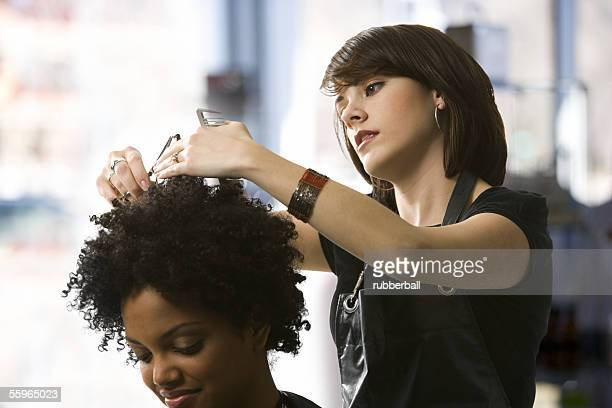 Female hairdresser trimming a young woman's hair