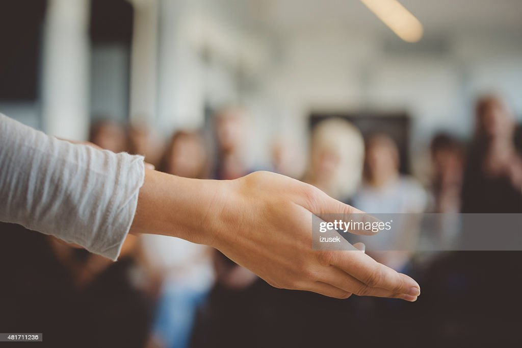 Female hand against defocused group of students : Stock Photo