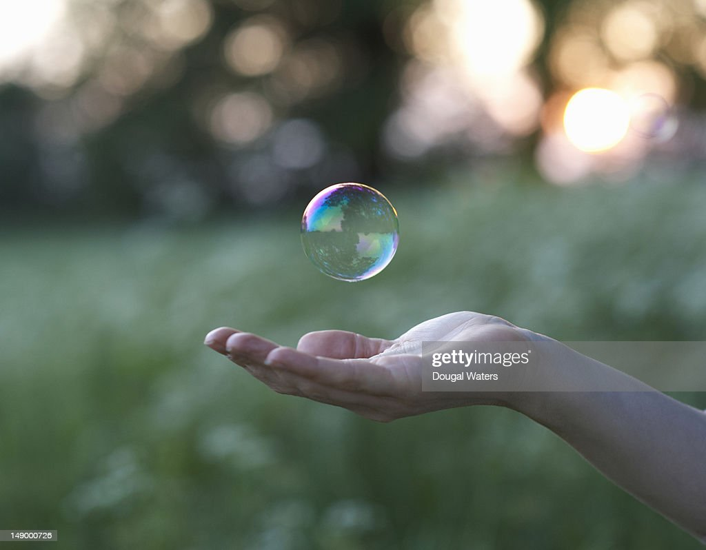 Female hand and floating bubble. : Stock Photo