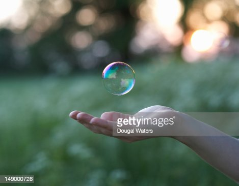 Female hand and floating bubble.