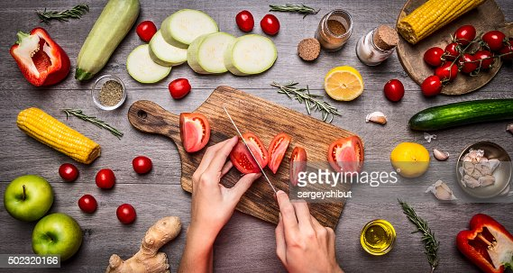 Female hand cut tomatoes rustic kitchen table,vegetarian concept. : Stock Photo