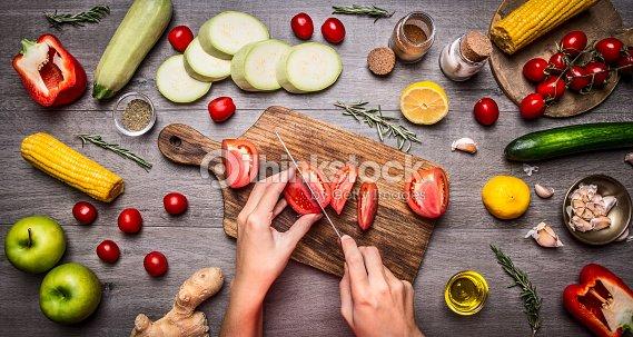 雌のハンドカットのトマト素朴なキッチンテーブル、ヴェジタリアン料理をお召し上がりいただけます。 : ストックフォト