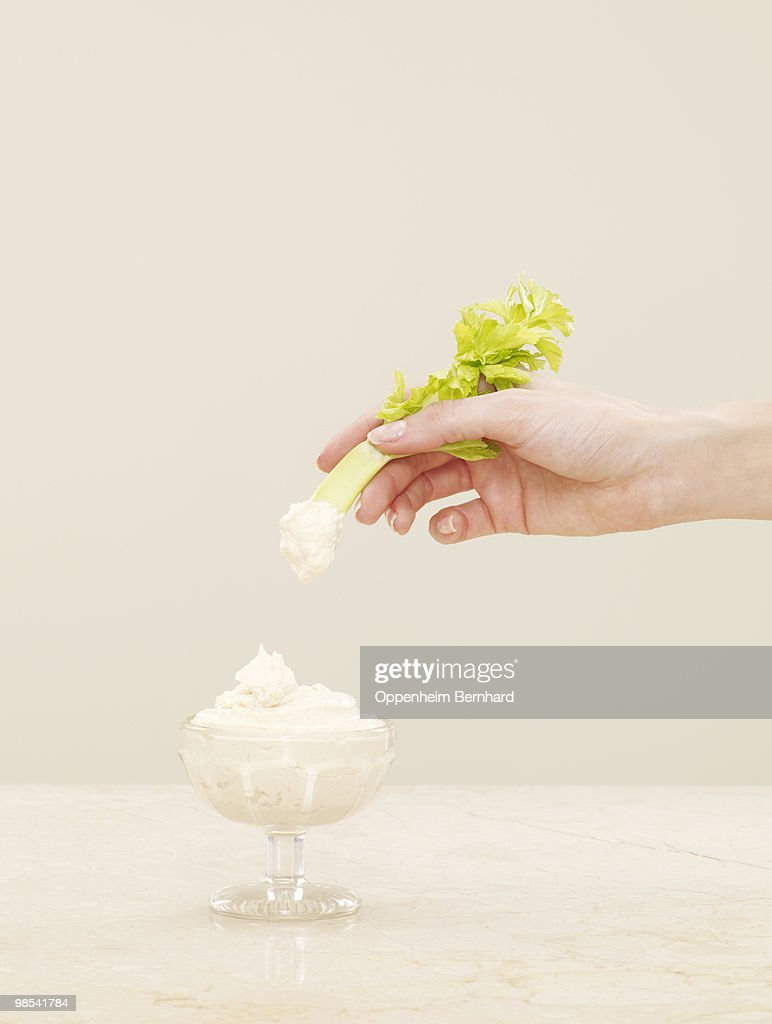 female hand dipping celery into pot of humous : Stock Photo