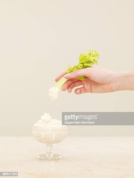 female hand dipping celery into pot of humous