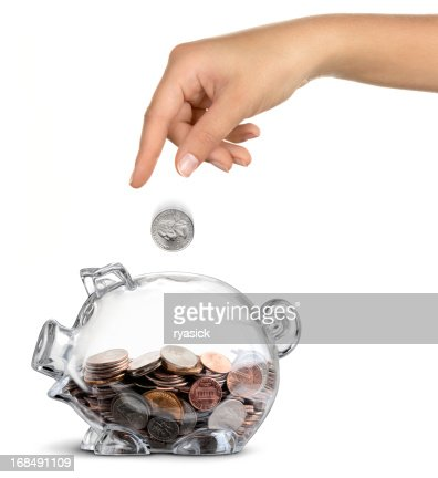 Female Hand Dropping Coin into Clear Half-filled Piggy Bank Isolated