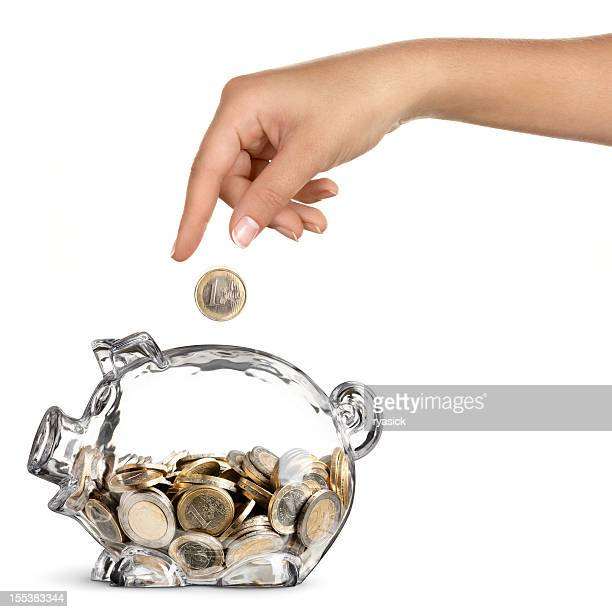 Female Hand Dropping Euro into Half Full Piggy Bank