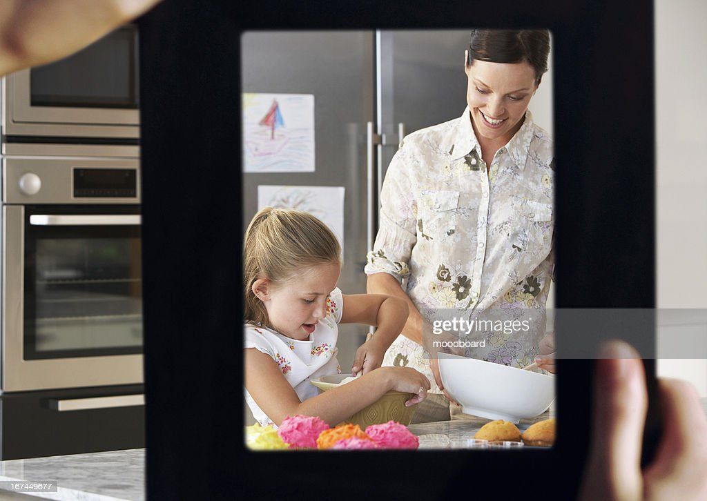 Female hand framing mother and daughter baking together in kitchen : Stock Photo