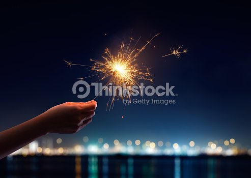 Female hand holding a burning sparkler : Stock Photo