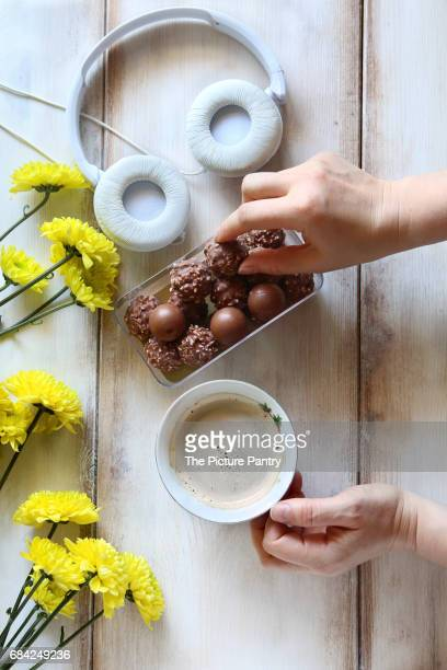 Female hand holding a cup of coffee and serving chocolate candy.Yellow daisy and headphones on the table