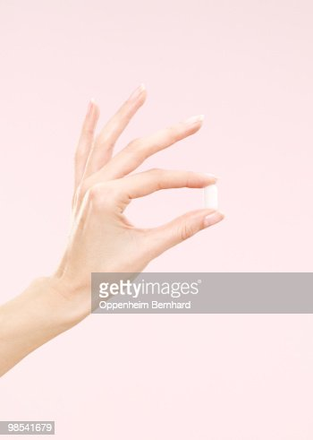 female hand holding a single tablet : Stock Photo