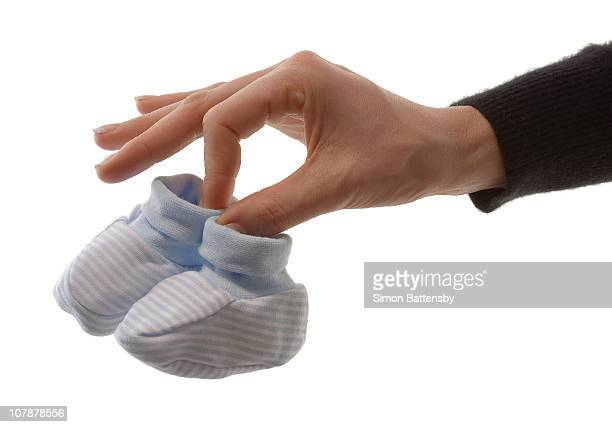 Female hand holding baby booties.