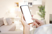 Female hand holding blank screen mobile smart phone over living room.