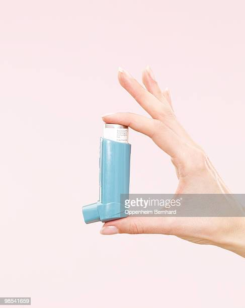 female hand holding blue inhaler