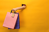 Female hand holding bright shopping bags on yellow