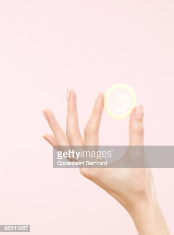 female hand holding condom : Stock Photo