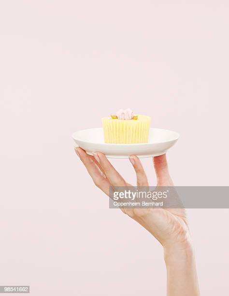 female hand holding cupcake on a white plate