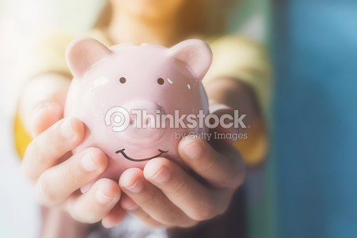 Female hand holding piggy bank. Save money and financial investment : Stock Photo