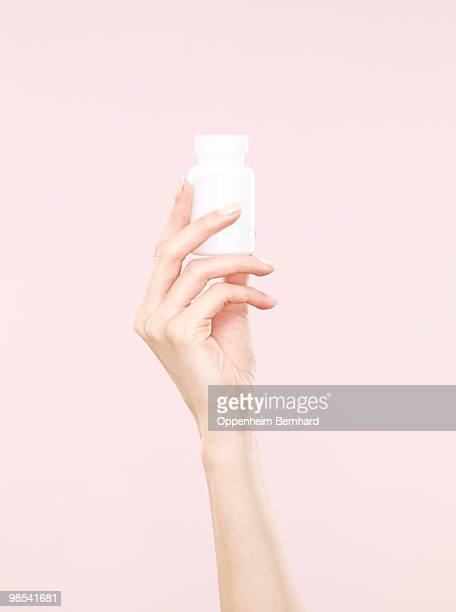 female hand holding tub of tablets