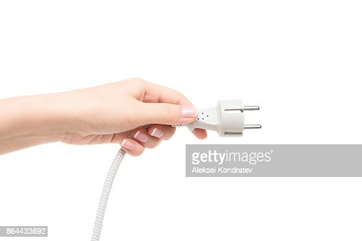 Female hand holds electric plug on a white background. : Stock Photo