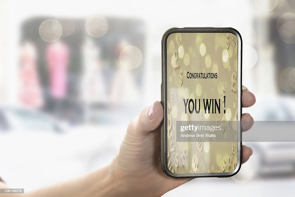 Female hand holds mobile phone with winning text : Stock Photo
