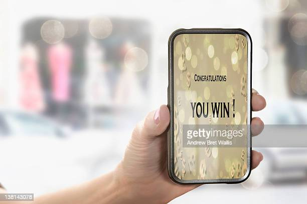 Female hand holds mobile phone with winning text