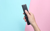 Female hand holds the TV remote on a pink  blue pastel background. Top View