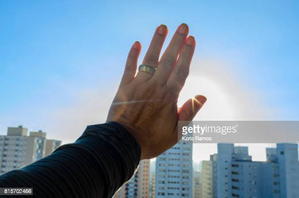 Female hand in the sky capping the sun on clear day and blue sky with buildings in the background in high angle in the city of São Paulo in Brazil