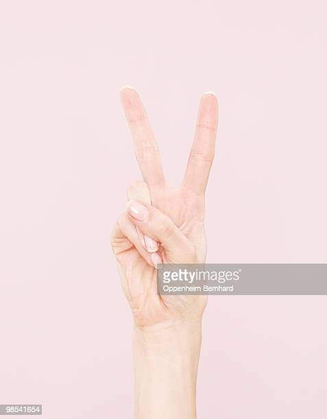 female hand making peace sign