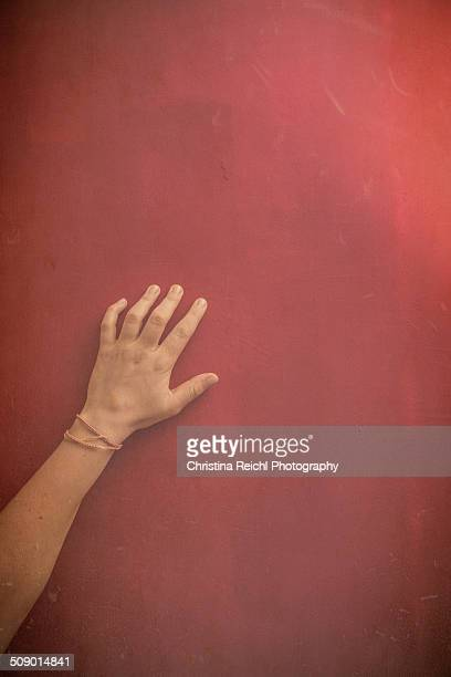 Female Hand on a red wall with textures