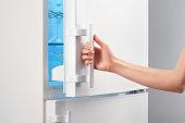 Female hand opening white refrigerator door on gray background