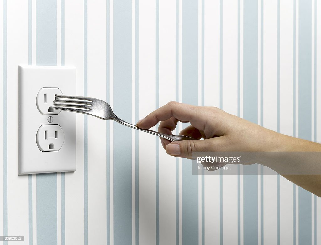 Female hand placing fork in outlet : Stock Photo