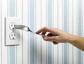 Female hand placing fork in outlet