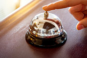 female hand presses the button of a bell in a hotel